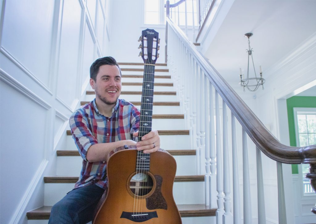 A photo of Daniel Barkley holding his guitar on a flight of stairs.